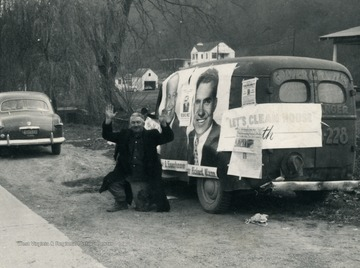 Man kneels beside van plastered in Dwight Eisenhower and Richard Nixon posters.