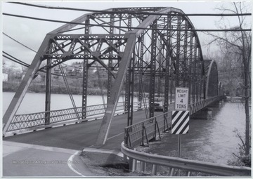 A car drives across the bridge that runs over Cheat Lake and along County Route 857.The bridge was built in 1922 by the Independent Bridge Company of Pittsburgh.