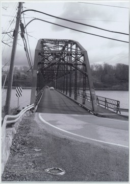 Two cars drive across the bridge that runs over Cheat Lake and along Country Route 857. The bridge was built in 1922 by the Independent Bridge Company of Pittsburgh.