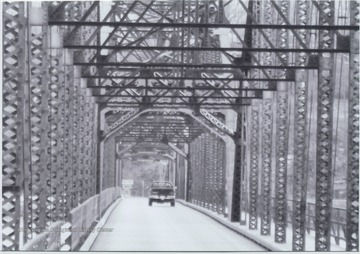 A lone car drives over the bridge that runs across Cheat Lake and along County Route 857. The bridge was built in 1922 by the Independent Bridge Company of Pittsburgh.