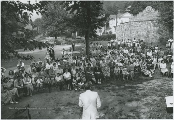 A crowd assembles on the lawn to hear a speaker. Subjects unidentified.