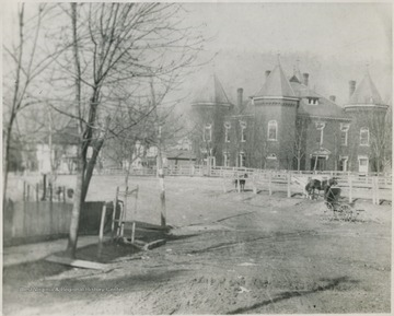 Looking at the building from across a field. A horse and old-fashioned baby stroller are pictured on the right.