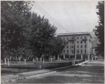 The square, to the left, is comprised of scattered trees and park benches. In the background is McCreery Hotel.