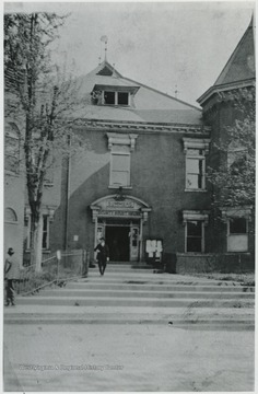 An unidentified man exits the courthouse, walking toward the steps that connect to the sidewalk.