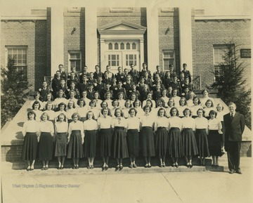 The group poses on the steps of the building. In the back row on the far left, Charles Lago is pictured. Other subjects unidentified.