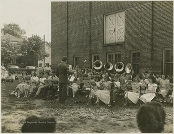 A band of young musicians plays outside Summers Memorial Building. Subjects unidentified.