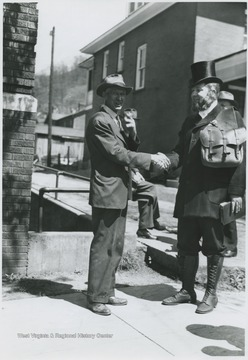 Moorman Parker, right, dressed as the rider for the re-enactment shakes hands with an unidentified man in front of the church located on 3rd Avenue.