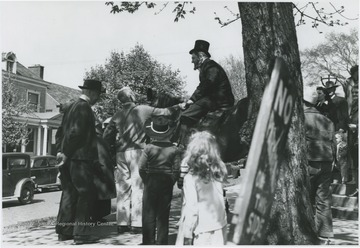 Moorman Parker sits on top of a horse to perform the re-enactment in front of the First Methodist church building located on the corner of Ballengee Street and Third Avenue. Other subjects and spectators unidentified.