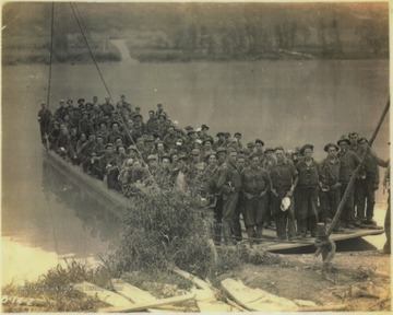 "A group of unidentified workers from the Civilian Conservation Corps pose on the ferry which was built to cross New River to save workers the hassle of having to drive to Hinton and cross the river at the old toll bridge. The ferry then took the men up the Bluestone River where ""the clearing of right of way was started"", according tot he photo caption."