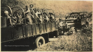 Civilian Conservation Corps members on the way to clear heavy timber for the Bluestone Dam right of way.