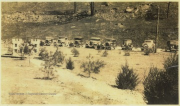 Automobiles belonging to the army, forest service personnel, and corps engineers are parked along the dirt road. The insignia formation is pictured on the left.