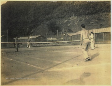 Members of the C.C.C. play a game of tennis. Stephen D. Trail, later an employee at Hinton Daily News, pictured shirtless on the right.