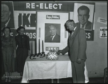 "An unidentified man cuts a cake to celebrate the birthday of President Dwight D. ""Ike"" Eisenhower. In the background hangs a campaign poster to re-elect Eisenhower as president with Richard Nixon as his vice-president."