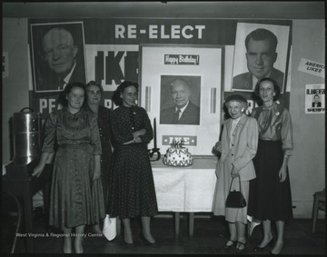 "A group of unidentified women stand around a birthday cake dedicated to President Dwight D. ""Ike"" Eisenhower's birthday. In the background hangs a campaign poster to re-elect Eisenhower as president with Richard Nixon as his vice-president."