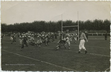 The high school football team plays an unidentified team. Players also unidentified. A referee looks on as a player runs with the ball.
