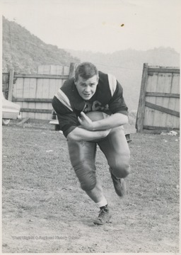 A football player at Hinton High School, Bennett is pictured in his team uniform running while cradling a football.