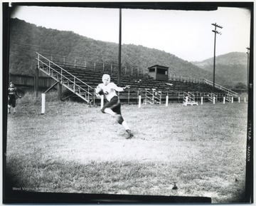 Shires, a football player for the Hinton High School Bobcats, pictured running with a football.