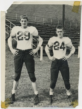 Dick Gunnoe, left, and David Hess, right, pictured in their team uniforms in front of the bleachers.