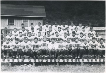 "Front row, left to right: Dick Maynard; Tommy Hartley; Jack Dillon; George Harris; albert Morgan; Coach Stanley Huffman; Kay Rogers; Tommy dodd; Dick Withrow; Virgil Moore; Marshall Vansant; and Bill ""Stud"" Bennet.Second row, left to right: K. D. Foster; Teddy Elmore; Georgie Cales; ""Sug"" Shull; Paul ""Foodie"" Phillips; Bill Scruggs; Gene ""Mule"" Bennet; Tom Pack; Jimmy Hartley; Don Wilson; and Charles ""Dadburn"" Dobbins.Third Row, left to right: Elraydo Johnson; Snooks Dobbins; Dick Fridley; Howard ""Curley"" Williams; John Gilbert; Jimmy Jarrett; Benny Neely; ""Pete"" Bishop; ""Bootie"" Bennett; and Jimmy Harvey.Fourth row, left to right: ""Morty"" Meadows; David Lively; Jimmy Burton; Carl Leach; Boyd Vansicle; Stanley Ferguson; Robert Morris; W. C. Parker; and Tommy Hallarow."