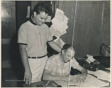 Weaver, right, signing a check to become the first member of the boosters club. This check, which appeared in The Hinton Daily News, caused 500 additional members and $1,500 to be raised by Jack Ball, pictured on the left. Ball became the first President of the boosters club.