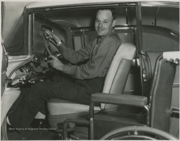 Freeland sits in the driver's seat of an automobile.