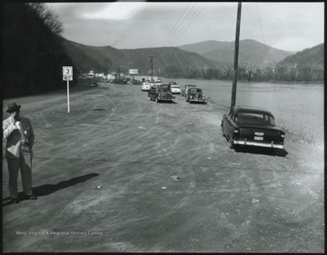 Automobiles line along the New River's shore line so their passengers may observe the view.