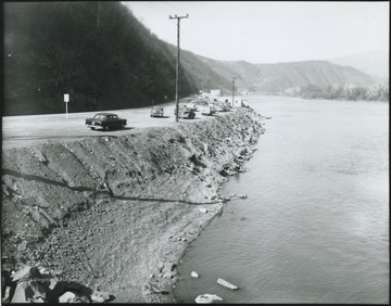 Automobiles line along the west side of the river so that their passengers can look out from the shore.