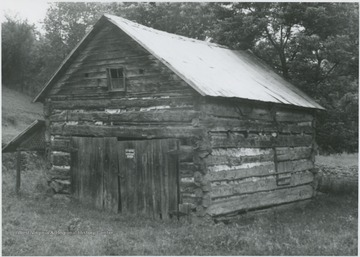 "The log cabin is located across a ""hard road and bridge"" from Blaker's Mill, according to the caption on the back of the photograph. Today, the old cabin is used as a barn."