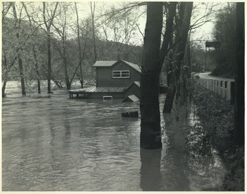Old Kozy Cove, an establish beer joint, is pictured mostly submerged in flood waters. To the right is Route 3.