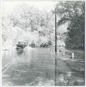 Two cars are seen splashing through the waters of the gradually submerged road.