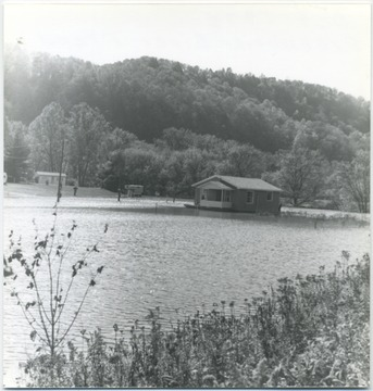 A house stands alone in the middle of the high rising waters. A person can be seen on the porch observing the situation.