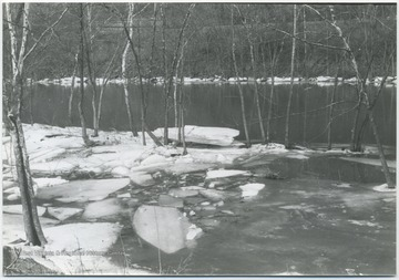 Ice blocks and snow cover the river banks.