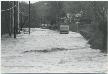 A truck makes its way through the road flooded by the  Greenbrier River. Two cars are also seen in the background attempting the same journey.