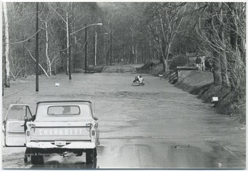 A Chevy truck is stopped in front of a submerged part of a road while two unidentified persons row toward it.