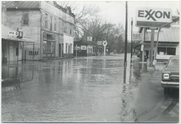 View of a submerged street with buildings on either side. Waters reached anExxon station to the right.