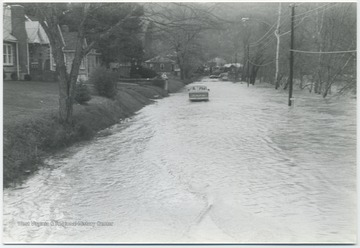 Flood waters from the Greenbrier River make driving difficult for the car pictured.