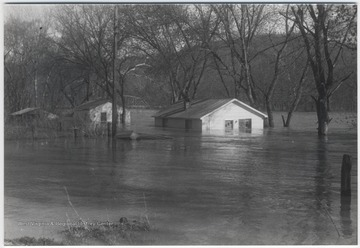 Three houses are pictured mostly under water.