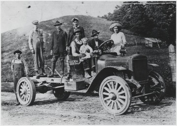 A group of men, dressed in overalls and working boots, stand on the back of the automobile. A man holding a child sits in the passenger seat with an associate driving. A woman is also pictured behind the car. Subjects unidentified.