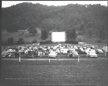 Automobiles cover the lawn in front of the movie screen.