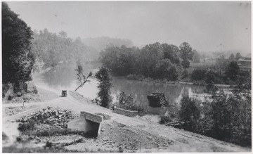 A lone automobile travels on the dirt road that runs alongside the river. The Piers are from a Glen Ray Lumber Company construction site where a railroad bridge is in the process of being built.