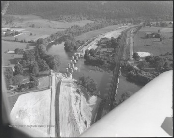 Aerial photograph looks over the river and banks. There appears to be a bridge being constructed parallel to the railroad bridge already in place.