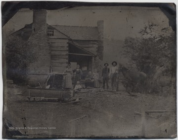 Family members pose outside of their log home with a horse. Subjects unidentified.