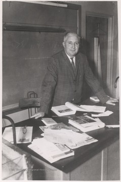 Hedrick, pictured at his book-covered desk, was a teacher at the high school. Note the fractions and number lines drawn on the chalkboard, implications that Hedrick taught mathemathics.