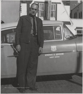 Keaton stands beside the U. S. Department of Agriculture's Forest Service automobile.Keaton was born June 13, 1913 and his father was L. B. Keaton, the former sheriff. G. E. Keaton married Elizabeth Kelly in 1935 and fathered two girls, Margaret and Elaine.
