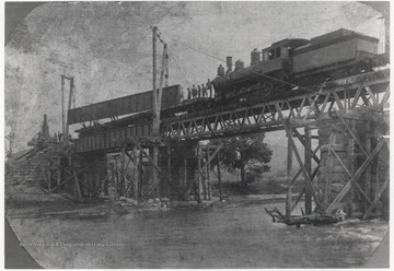 Workers scatter across the construction site. Cranes helps lift supplies onto the bridge. A train is pictured on top of the bridge, perhaps bringing in additional supplies.