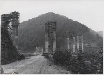 Large supporting structures tower over a smaller bridge connecting a dirt road.