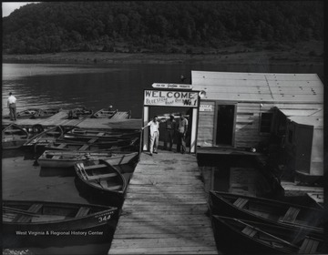 "Three unidentified men stand beneath a sign that reads, ""Welcome--Bluestone Boat Dock No. 1"". Empty row boats surround the dock."