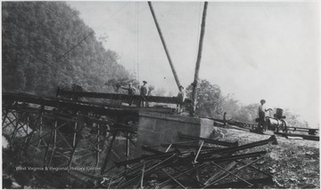 A group of unidentified men stand beside the construction equipment at the site of the bridge to go over the mouth of the Bluestone River.