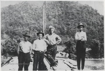 The unidentified men stand at the site located above the mouth of the Bluestone River.