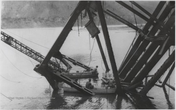 Five workmen killed and four injured when the 300-ton span buckled and folded downward into the river. A week after the collapse the men began dismantling the twisted span, using a never before used technique by burning the steel beams with chemicals.